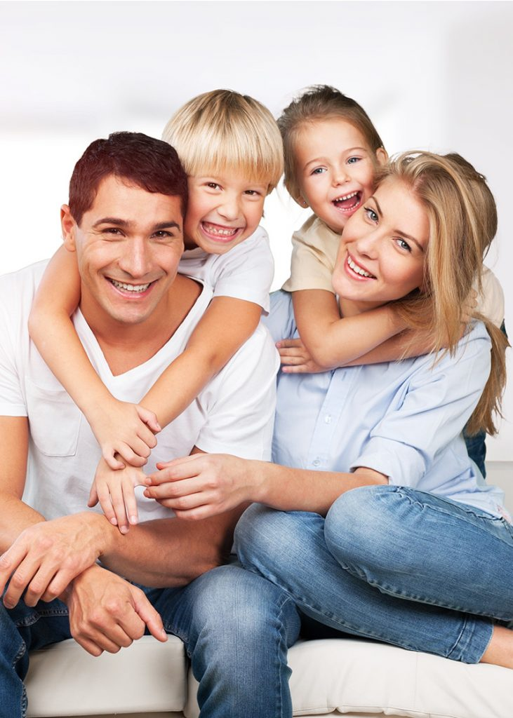 Young white family at home smiling at camera