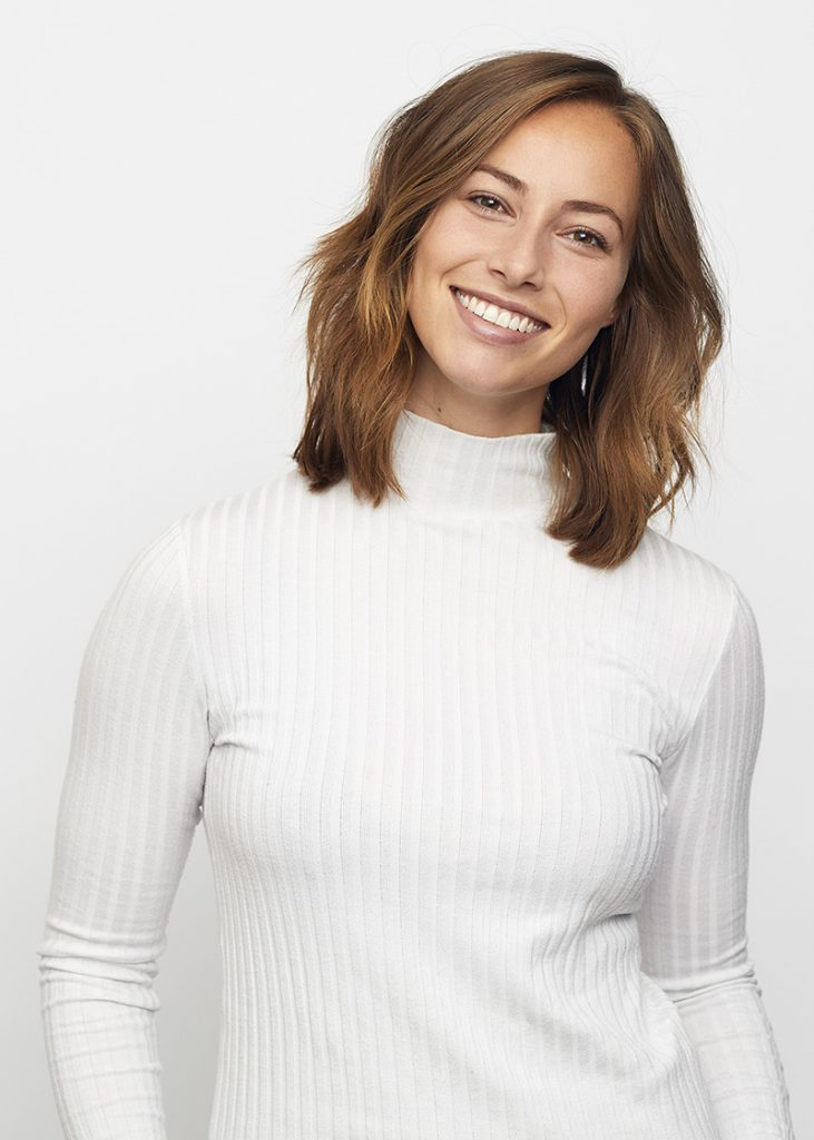 Young woman smiling at camera with white background.