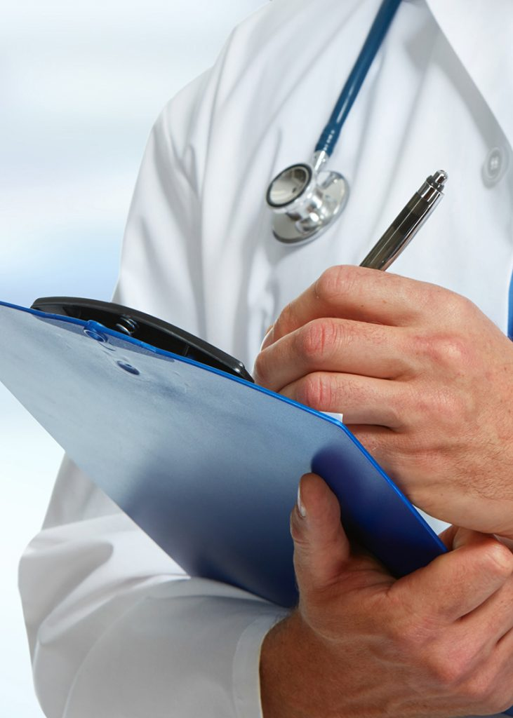 Doctor with stethoscope around his neck holding pen to a medical chart on a clipboard.