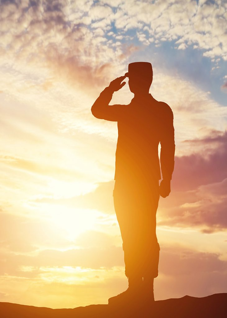 Soldier saluting with the sunset behind him