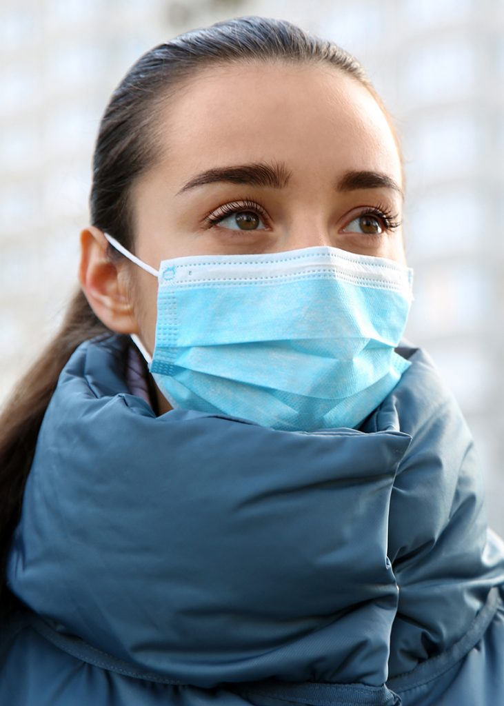 Brown haired white woman wearing winter jacket and blue disposable face mask.