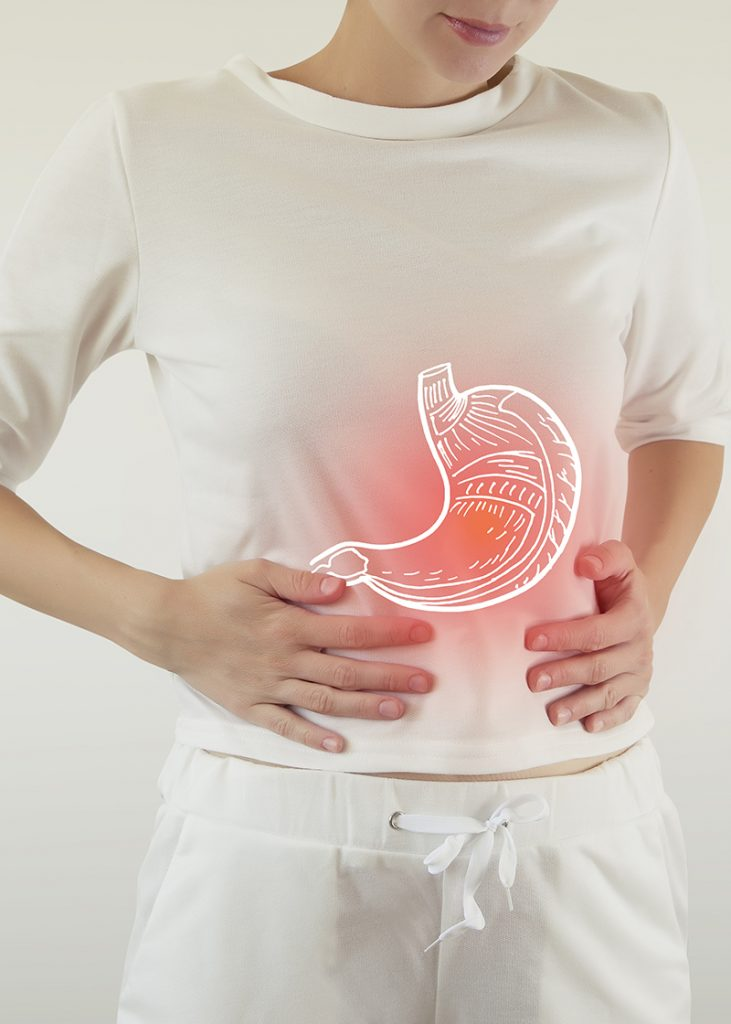 Digital illustration of inflamed stomach depicted by woman holding her abdomen and red glowing light around illustration to indicate pain.